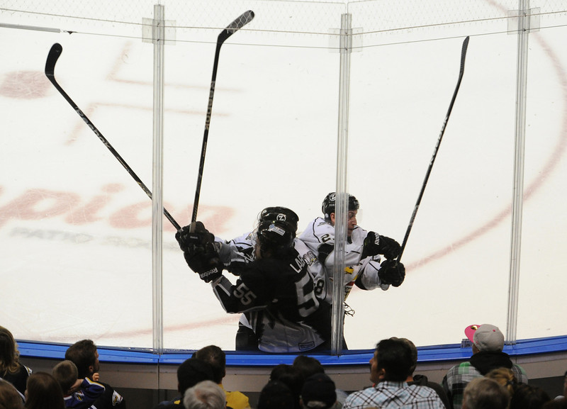 Colorado Eagles forwards A.J. Hau, rear, and Dylan Hood, right, check Idaho Steelhead Hubert Labrie into the glass during the second period of play during a Colorado Eagles playoff game Sunday night at the Budweiser Event Center in Loveland, Colo.