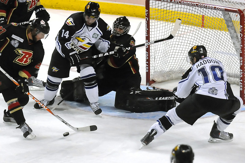 Colorado Eagles winger Steve Haddon, right, and forward Daymen Rycroft battle in front of the net with Rapid City Rush goalie Tim Boron and defenseman Dave Grimson in the second period of their game Thursday, May 5, 2011 at the Budweiser Events Center in Loveland, Colo.