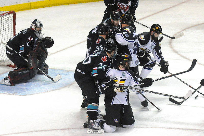 Colorado Eagles players Adam Hogg, right, Aaron Schneekloth (23) and Steve Haddon battle for control of the puck in the third period of their game against the Bossier-Shreveport Mudbugs on Friday, May 27, 2011 at the Budweiser Events Center in Loveland, Colo.