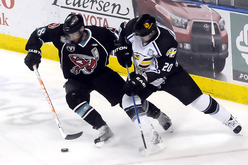 Bossier-Shreveport Mudbugs winger Justin Aikins, left, battles for control of the puck with Colorado Eagles defenseman Jason Beatty in the first period of their game on Friday, May 27, 2011 at the Budweiser Events Center in Loveland, Colo.
