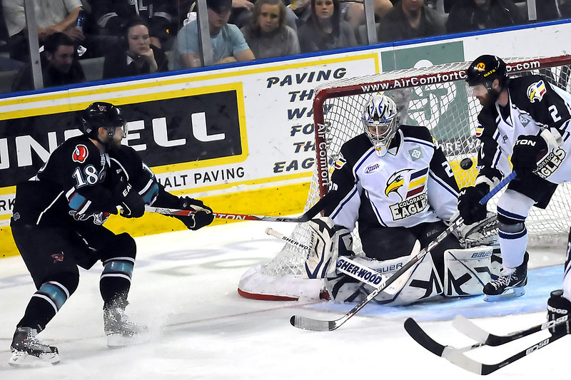 Bossier-Shreveport Mudbugs winger Justin Aikins, left, takes a shot on Colorado Eagles goalie Kyle Jones while defenseman Kip Workman looks on in the second period of their game on Friday, May 13, 2011 at the Budweiser Events Center.