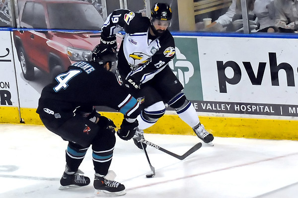 Colorado Eagles center Adam Hogg, back, tracks down the puck in front of Bossier-Shreveport Mudbugs defenseman Clay Plume in the second period of their game Saturday, May 14, 2011 at the Budweiser Events Center.