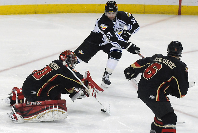 Colorado Eagles forward Dylan Stanley (51) tries to get the puck past Rapid City Rush goalie Danny Battochio and defenseman Riley Weselowski in the first period of their game on Wednesday, Nov. 24, 2010 at the Budweiser Events Center.