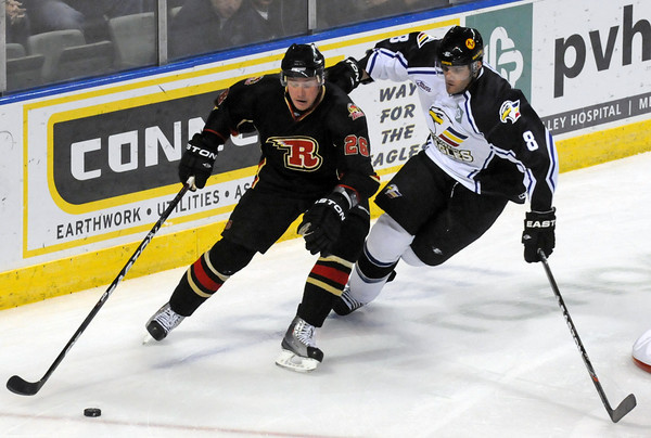 Colorado Eagles defenseman Chris Hau, right, and Rapid City Rush defenseman Jamie VanderVeeken track down the puck behind the net in the first period of their game on Wednesday, Nov. 24, 2010 at the Budweiser Events Center.