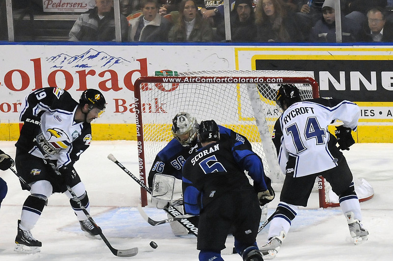 Colorado Eagles teammates Adam Hogg, left, and Daymen Rycroft battle in front of the net with Wichita Thunder goalie Marty Magers and defenseman Kory Scoran in the first period of their game on Friday, Nov. 26, 2010 at the Budweiser Events Center.