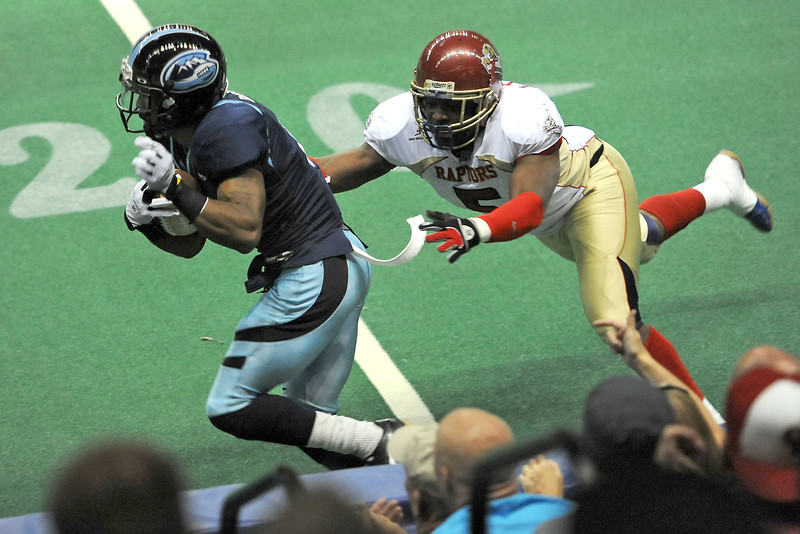 Colorado Ice wide receiver Duane Brooks, left, eludes the grasp of Everett Raptors linebacker Leandre Walner after making a catch in the second quarter of their game Saturday, March 31, 2012 at the Budweiser Events Center.