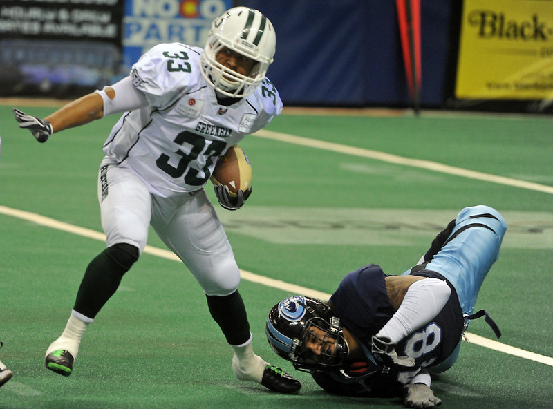 Green Bay Blizzard runningback Levell Coppage (33) slips the tackle of (number 48, defense, ice) in the first quarter during a game at the Budweiser Event Center, Sunday in Loveland, Colo.