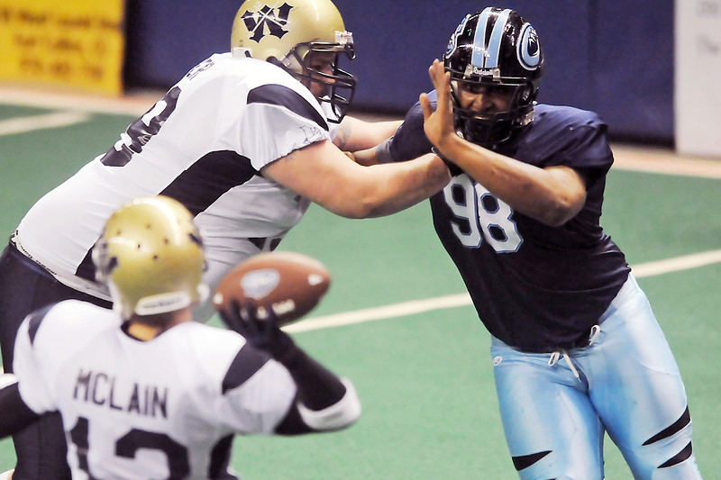 Colorado Ice defensive lineman Brandon Fanney, right, fights around a block by Wyoming Cavalry lineman Nolan Fisher to get at quarterback Joe McClain in the second quarter of their game on Sunday, April 17, 2011 at the Budweiser Events Center. The Ice won, 59-54, to remain undefeated on the season.