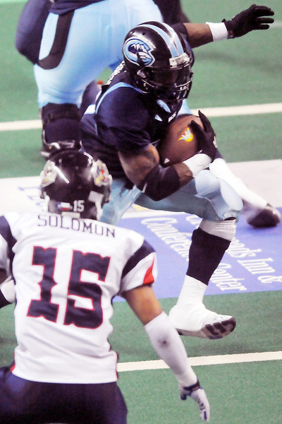 Colorado Ice running back Terry Washington makes a carry around Allen Wranglers defensive back Frankie Solomon (15) in the first quarter of their game Saturday night at the Budweiser Events Center.