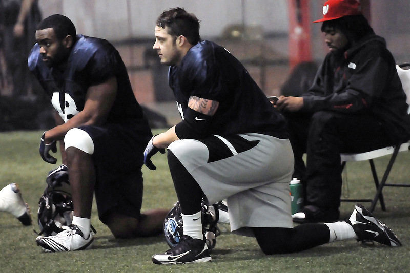 Colorado Ice defensive linemen Chase Vaughn, left, and Dominic Applehans each take a knee on the sideline during practice Thursday, March 3, 2011 at Arena Sports in Windsor.