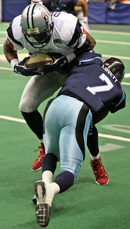 Ice defensive back CJ Lovett (7) tackles wide receiver Terrell Owens (81) along the sideline during the 2nd half Sunday at the Budweiser Events Center. The Colorado Ice handed the Allen Wranglers their first defeat of the season, 61-55, despite their marquee player's appearance.