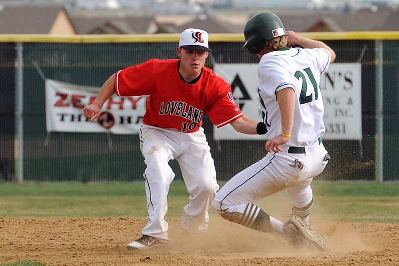 Loveland High School's Kylen Bakovich, left, tags out Fossil Ridge baserunner Tyler Thompson on a steal attempt in the bottom of the fourth inning of their game Thursday, April 12, 2012 at FRHS.
