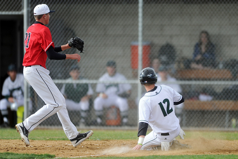 Fossil Ridge High School baserunner Corey Peter slides into home plate for a steal ahead of the tag attempt by Loveland pitcher Alec Hansen on a passed ball in the bottom of the second inning of their game Thursday, April 12, 2012 at FRHS.