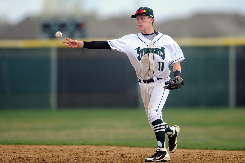 Fossil Ridge High School second baseman Logan Waterland makes the throw to first base for an out after fielding a ground ball in the top of the fifth inning of a game against Loveland on Thursday, April 12, 2012 at FRHS.