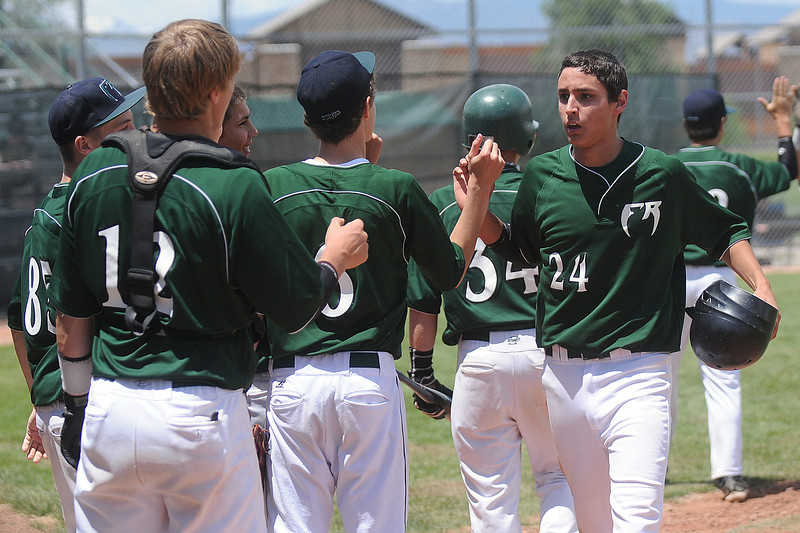 Fossil Ridge High School's Julian Garcia (24) is congratulated by teammates outside the dugout after scoring a run in the bottom of the fourth inning of a game against Advocare on Saturday at Brock Field.