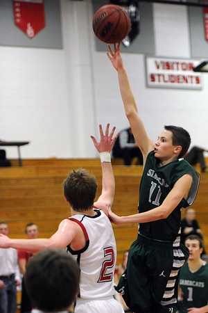 Fossil Ridge High School sophomore Evan Smith, right, puts up a shot over Loveland's Ryan Andrews in the second quarter of their game Tuesday, Feb. 14, 2012 at LHS.