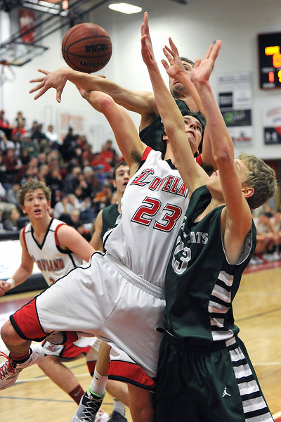 Loveland High School senior Adam Kinnes, middle, is fouled as he goes up for a shot between Fossil Ridge's Alex Semadeni, right, and Garrett Bryant in the first quarter of their game Tuesday, Feb. 14, 2012 at LHS.