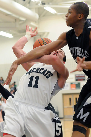 Fossil Ridge High School senior Zach Chavez-Levett (11) is fouled as he goes up for a shot by Montbello's Karamoko Cisse in the second quarter of their game on Wednesday, Mar. 2, 2011 at FRHS. The SaberCats won, 60-57.