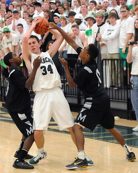 Fossil Ridge High School senior Alex Blum (34) looks for an open teammate while being pressured by  Montbello defenders Isiah Cooper, left, and Jawaun McFalls in the third quarter of their game on Wednesday, Mar. 2, 2011 at FRHS. The SaberCats won, 60-57.