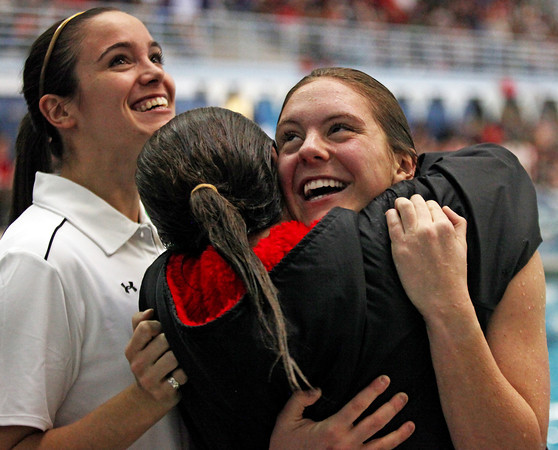 Loveland junior diver Michal Bower, right, gets congratulations from senior Chanley Burge Saturday, center, and Loveland dive coach Elyse Jackl, left, after winning her third consecutive state dive title, becoming only the third diver to ever accomplish this feat in state history.