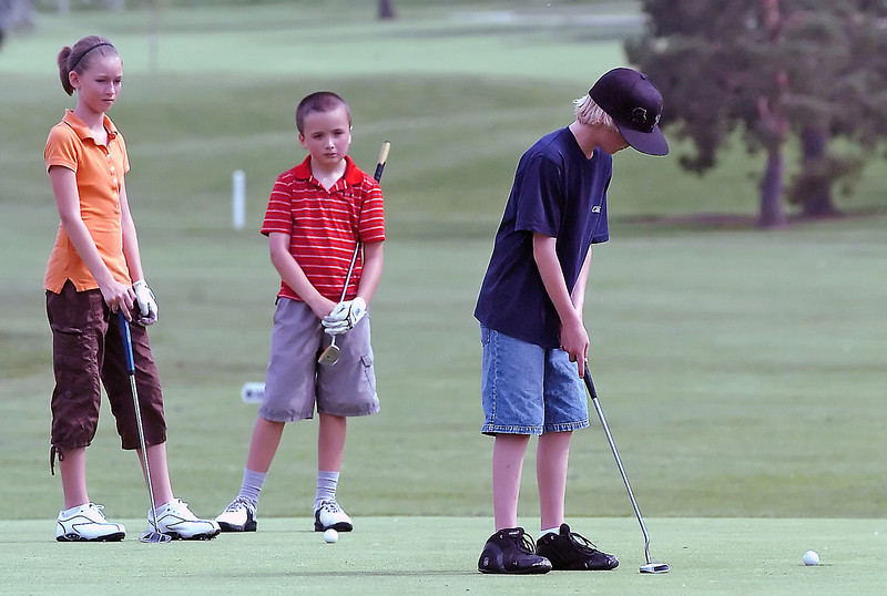Hannah Doran, 11, left, and Drew Mettler, 10, look on while Mitchell Leach, 11, sinks his putt on hole 7 during the Loveland Breakfast Optimists Junior Golf Tournament on Monday, June 7, 2010 at The Olde Course at Loveland.