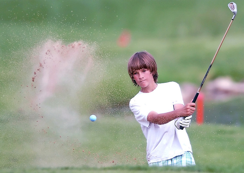 Lucas Beal, 13, blasts out of a sandtrap and onto eighth hole green during the Loveland Breakfast Optimists Junior Golf tournament on Monday, June 7, 2010 at The Olde Course at Loveland.