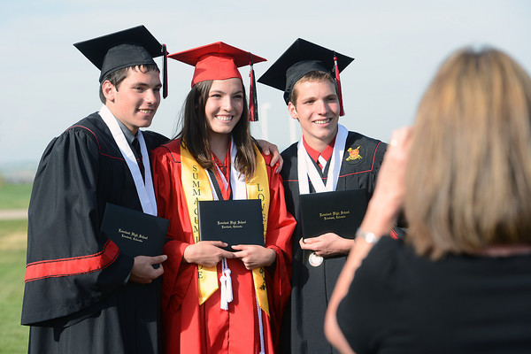 Siblings, from left, Alex Spencer, Lauren Spencer and Matthew Spencer pose together while their aunt Janelle Aigner takes their picture after the triplets graduated together from Loveland High School during a ceremony on Saturday, May 25, 2013 at the Budweiser Events Center.