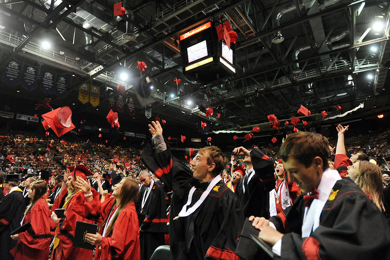 Loveland High School's Austin Anderson, right, and Brett Johnson toss their mortar boards into the air with classmates at the end of their graduation ceremony on Saturday, May 25, 2013 at the Budweiser Events Center.