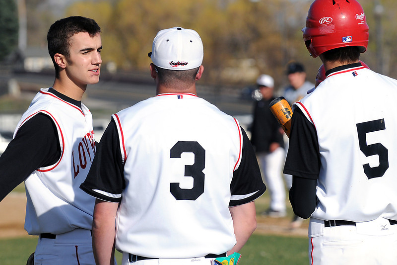 Loveland High School senior Darius Coldiron, left, talks to head coach Jake Marshall (3)  and teammate Cam Michael (5) during their game against Fossil Ridge on Friday, April 15, 2011 at Swift Field.