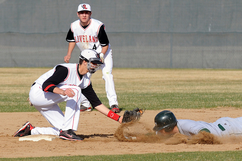 Loveland High School shortstop Darius Coldiron, left, tags out Fossil Ridge's Tanner McPhee while second baseman Mason Flores looks on in the top of the fifth inning of their game Friday at Swift Field. The Indians won, 10-8.