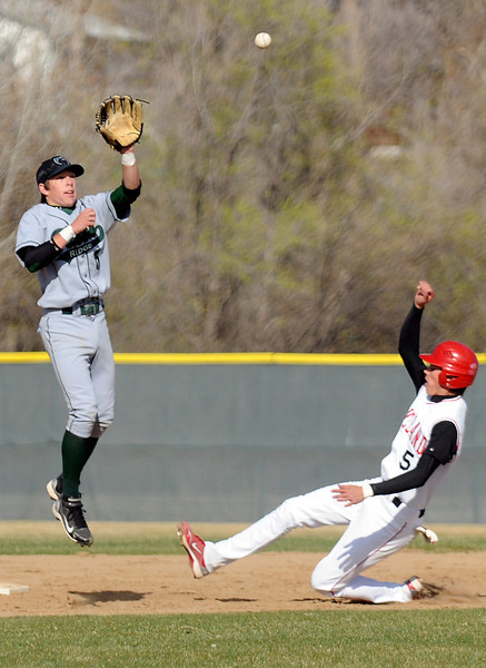 Loveland High School senior Cam Michael, right, slides safely into second base for a steal ahead of the throw to Fossil Ridge's Kyler Eubank in the bottom of the fourth inning of their game Friday at Swift Field. The Indians won, 10-8.