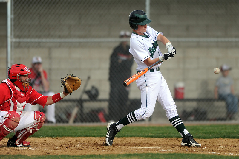 Fossil Ridge High School's Hunter Donaldson swings at the ball for a single while Loveland catcher Matt Walkowicz looks on in the bottom of the fourth inning of their game Thursday, April 12, 2012 at FRHS.