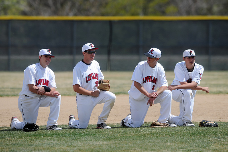 Loveland High School infielders, from left, Kylen Bakovich, Jay Larson, Seth Schroeder and Ryan Baca kneel together during a pitching change in top of the fourth inning of their game against Fairview on Saturday, April 14, 2012 at Swift Field.