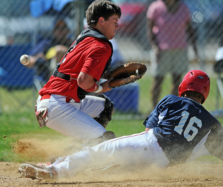 Catcher of Davidson-Gebhardt mishandles the ball as 16 of the Post 6 Hawks slides in for a run in the bottom of the 6th inning of Wednesday's game at Don Constantz Field at Thompson Valley High School. The Hawks took the game 4-1.