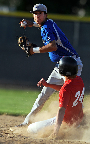 13 of Longmont throws to first as 24 of Davidson-Gebhardt slides into second during the bottom of the 6th inning of Wednesday afternoon's game at Swift Field in Loveland. Longmont won the game 16-1.