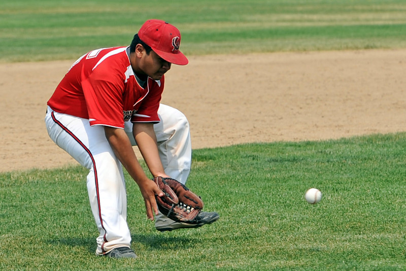 Third baseman Anthony Fernandez of Loveland High School's summer team Davidson Chevrolet fields a ground ball in the second game of a double header against Legion Post 7 from Cheyenne at Centennial Park on Wednesday, July 4, 2012.