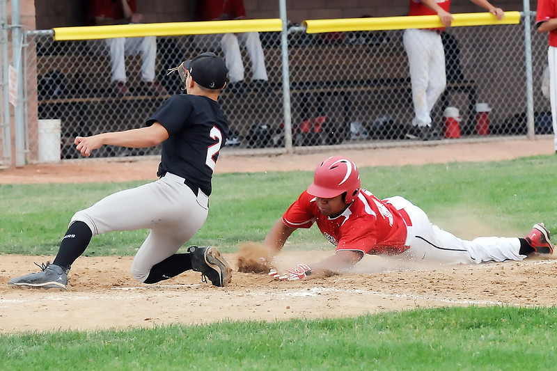 Davidson Chevrolet's Dalton Weiss slides safely into home ahead of the tag by Legion Post 70 pitcher Kane Kratz after a passed ball in the bottom of the third inning of their game Wednesday, June 29, 2011 at Swift Field.
