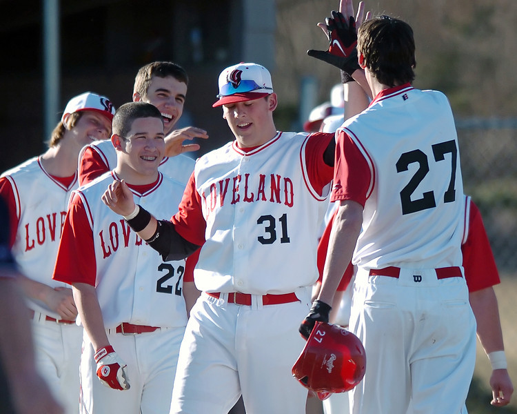 Loveland High School's Dominic East, right, gets a high-five from Darryl Baca (31) as he's congratulated by teammates after driving in the winning run in the fifth inning of a game against Thompson Valley on Tuesday, March 16, 2010 at Swift Field. Loveland won, 14-4, in the fifth inning.