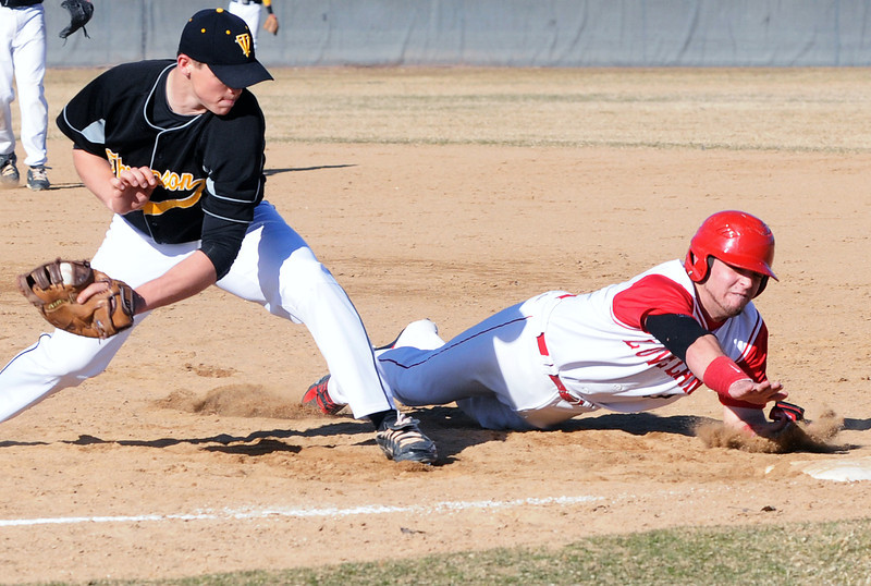 Loveland High School's Trent Lussenhop dives back to the first base ahead of the pickoff attempt by Thompson Valley first baseman Caleb Carlson on Tuesday, March 16, 2010 at Swift Field. Loveland won, 14-4, in the fifth inning.