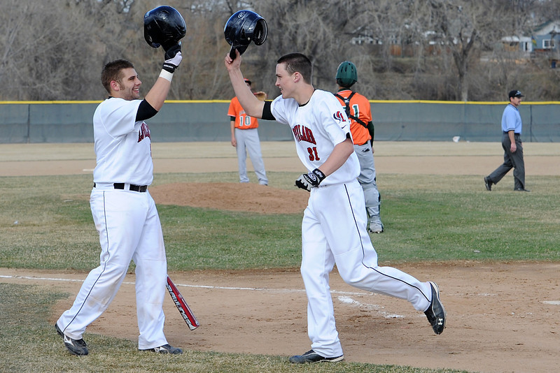 Loveland High School senior Matt Walkowicz, left, congratulates teammate Jake Weinmaster after he hit a home run in the bottom of the second inning of their game against Adams City on Friday, March 16, 2012 at Swift Field.