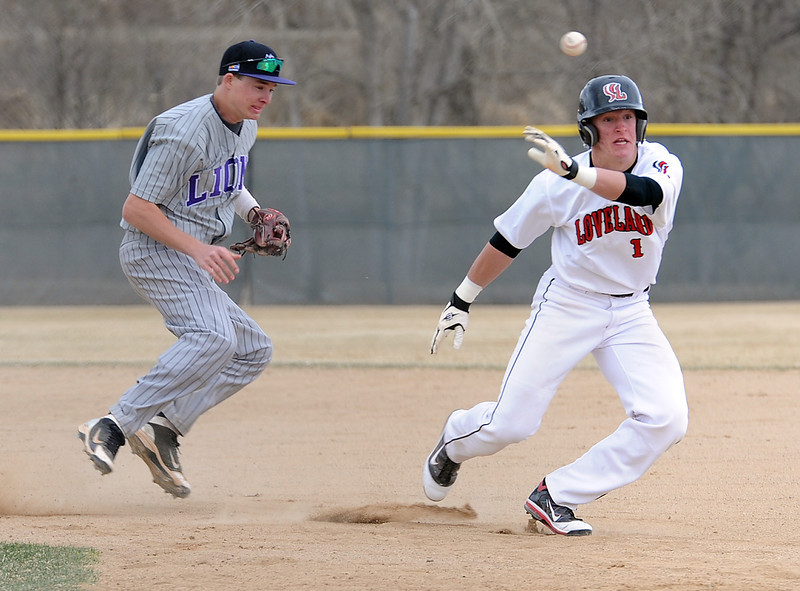 Mountain View #5 Kollin Evens, left, throws the ball back to first base from second as Loveland's #1 Greg Hecker runs back during a game Monday at Swift Field. Photo by Jenny Sparks