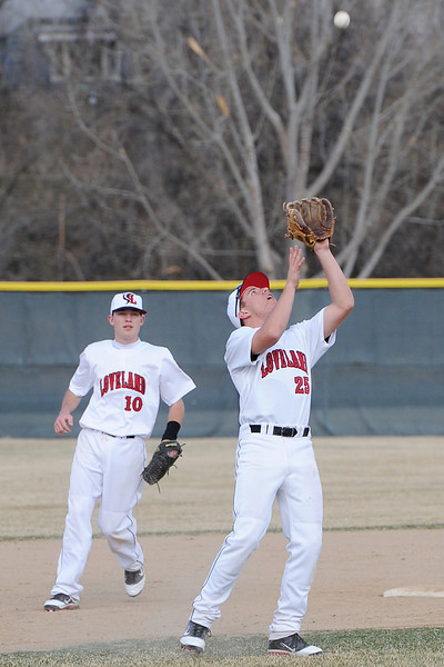 Loveland High School shortstop Jay Larson, right, catches a pop fly for an out while second baseman Kylen Bakovich looks on in the top of the third inning of their game against Adams City on Friday, March 16, 2012 at Swift Field.