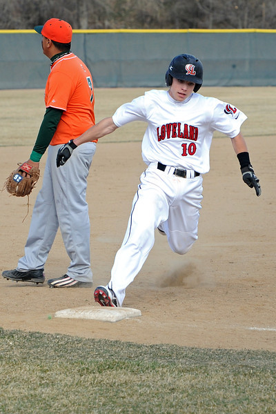 Loveland High School senior Kylen Bakovich (10) rounds third base on his way to scoring a run in the bottom of the second inning of a game against Adams City on Friday, March 16, 2012 at Swift Field.