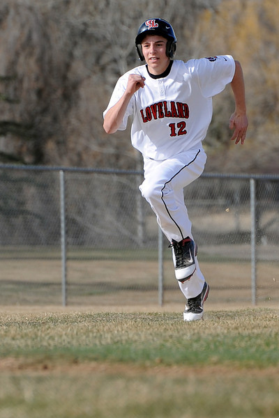 Loveland High School junior JC Schneider sprints down the third base line to score a run in the bottom of the first inning of a game against Adams City on Friday, March 16, 2012 at Swift Field.