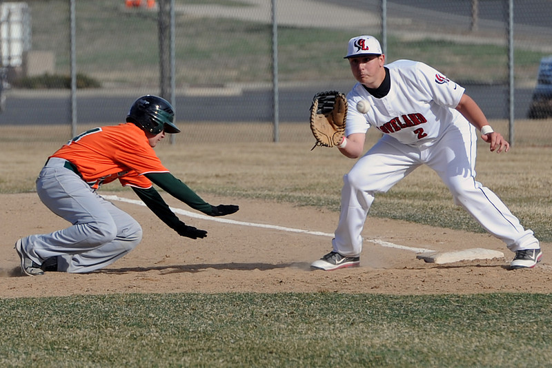 Adams City baserunner Fredy Renteria dives safely back to first base ahead of the tag attempt by Loveland's Ryan Baca in the top of the second inning of their game Friday, March 16, 2012 at Swift Field.