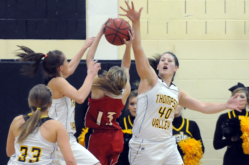 Loveland High School's Stephanie Hutsell, center, takes a shot between Thompson Valley High School defenders Jordan Sibrel, left, and Kenzie Archer while Alexis Hunt looks on in the first quarter of their game Friday at TVHS. The Eagles won, 50-39.