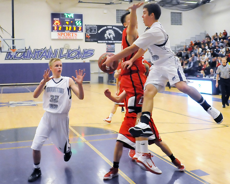 Mountain View High School senior Brennan Stine, right, makes a pass to teammate Josh Sandin around Loveland's Jim Etling in the fourth quarter of their game on Tuesday, Dec. 21, 2010 at MVHS.