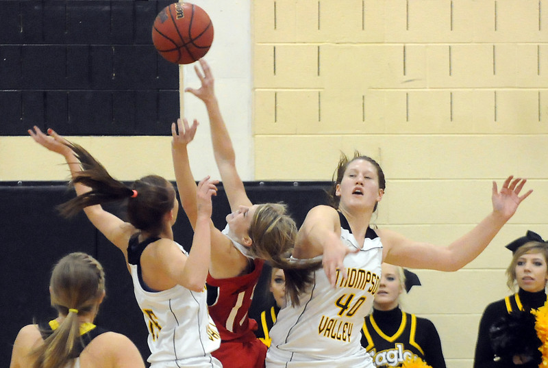 Loveland High School's Steph Hutsell, center, takes a shot between Thompson Valley High School defenders Jordan Sibrel, left, and Kenzie Archer while Alexis Hunt looks on in the first quarter of their game Friday at TVHS. The Eagles won, 50-39.