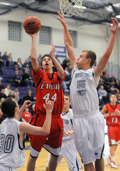 Loveland High School sophomore Conor Lang (44) puts up a shot between Mountain View's Spencer Stetler (30) and Zach Watson (55) in the third quarter of their game on Tuesday, Dec. 21, 2010 at MVHS.