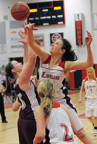 Loveland High School senior Stephanie Gramberg goes up for a rebound against Horizon's Amber Rasmussen while teammates Bradey King (2) and Amber Bechman (5) look on in the second quarter of their game on Tuesday, Feb. 9, 2010 at LHS.